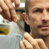 IBM scientist Dr. Mark Lantz, holds a one square inch piece of sputtered tape, which can hold 201 Gigabytes, a new world record. -IBM Research photo