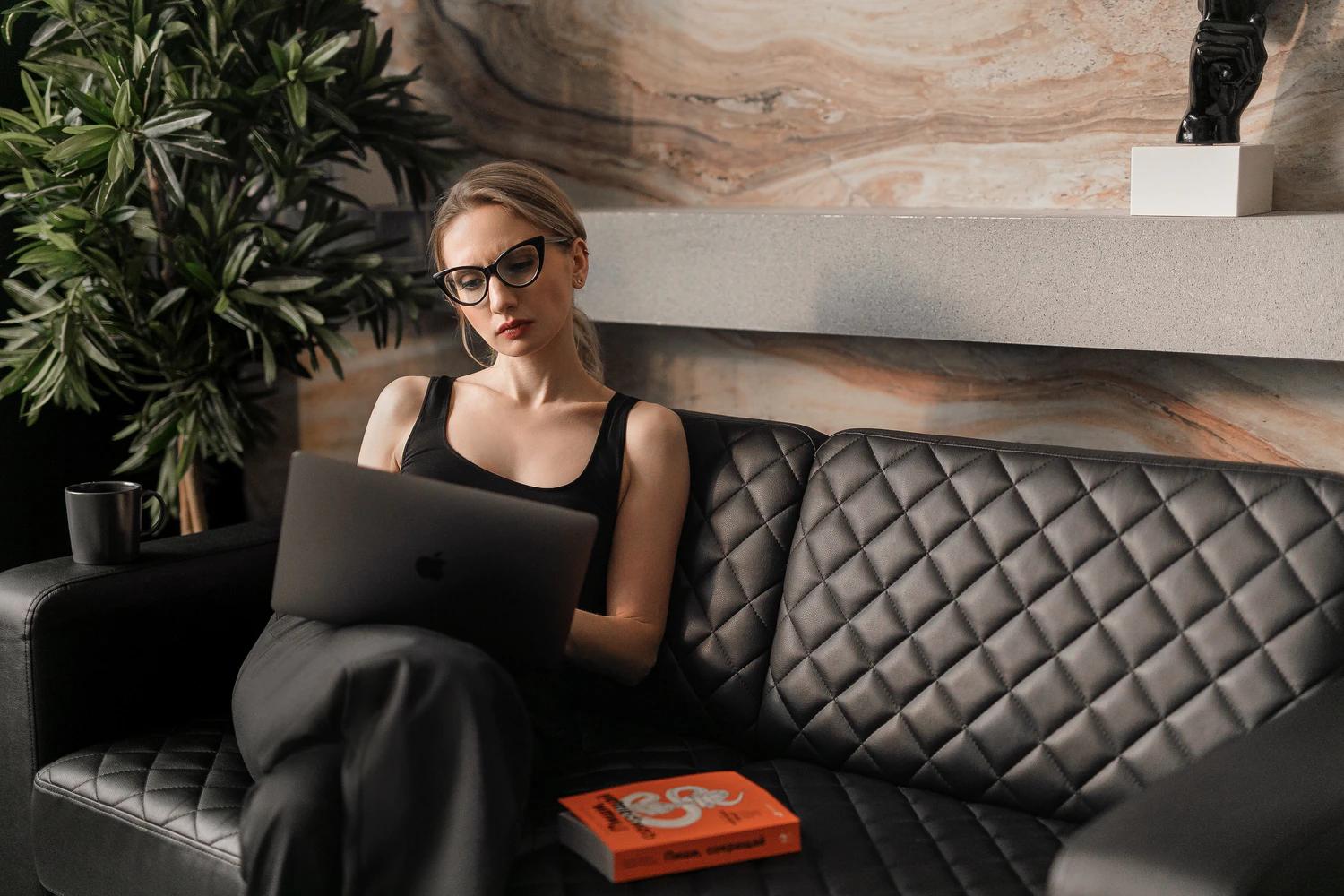 Woman sitting on a couch using a laptop